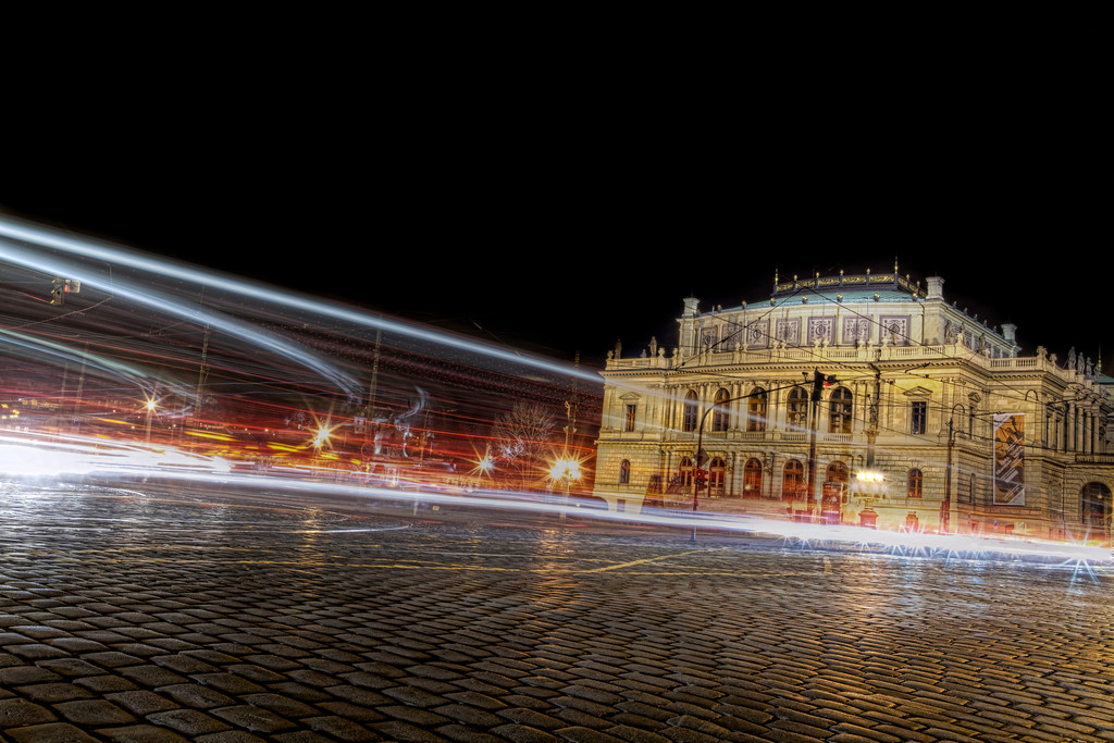 Czech Philharmonic at Rudolfinum in Prague at night with lights and cobblestones.