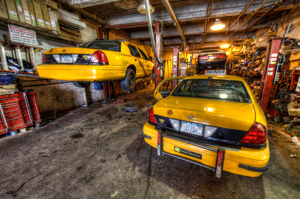 Long narrow garage for yellow taxi cabs in New York City with one up on a lift.