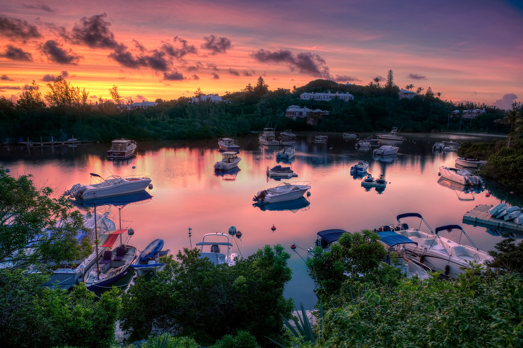 Boats on their moorings under a glorious purple sunset, reflecting pink in the water of Tuckers Town Bay in Bermuda.