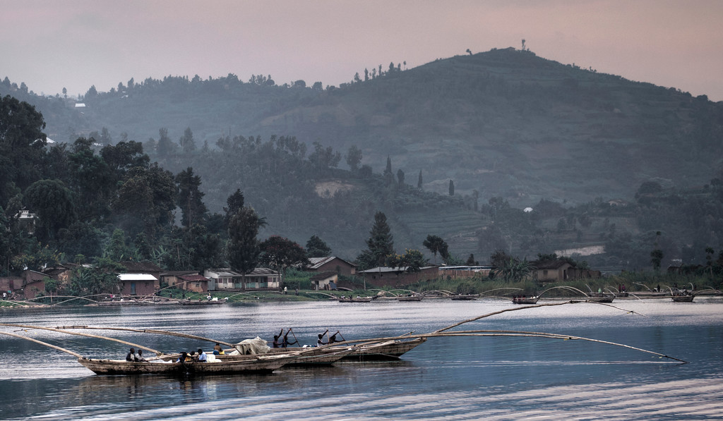 Lake Kivu, Rwanda fishermen leaving in canoes which are made of three hulls attached by beams and a spindly bit to hold the nets.