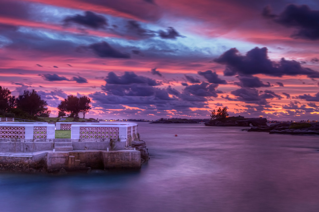 Surreal pink and blue sunset over Spanish Point, Bermuda with a water-edge backyard behind a low wall.