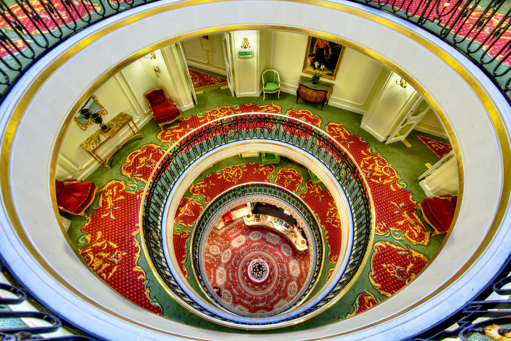 Dizzy view down from the top of the spiral staircase in The Ritz, London with bright red, green and yellow decorative carpeting.
