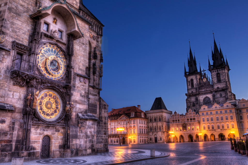 Astronomical clock and the Tyn Church in Old Town Square, Prague early morning under a blue sky.