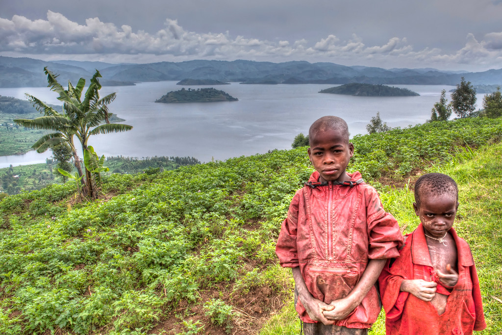 Portrait of two local boys dressed in red where the older looks very serious and wise in front of the twin lakes, Burera and Ruhondo, in Rwanda.