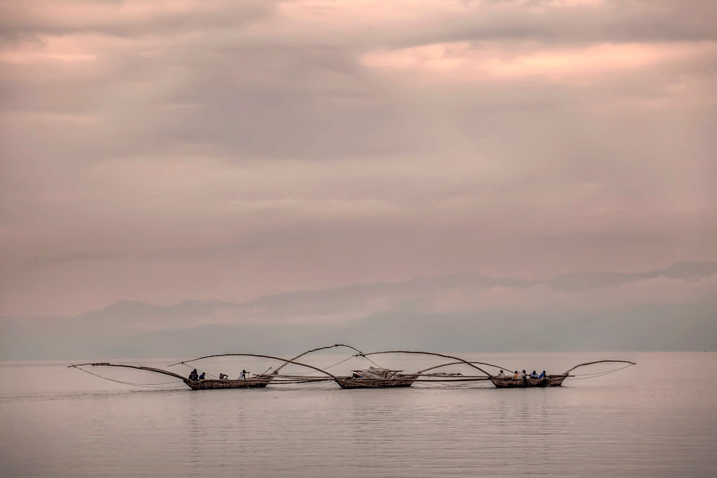 Fishermen on Lake Kivu, Gisenyi, Rwanda, heading out at night to work their nets from their triple hulled boat in search of talapia and little black sambassa.